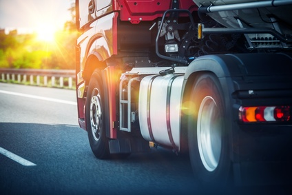 Red Semi Truck Speeding on a Highway. Tractor Closeup. Transportation and Logistics Theme.