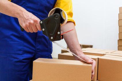 Closeup of a worker hands packing a box